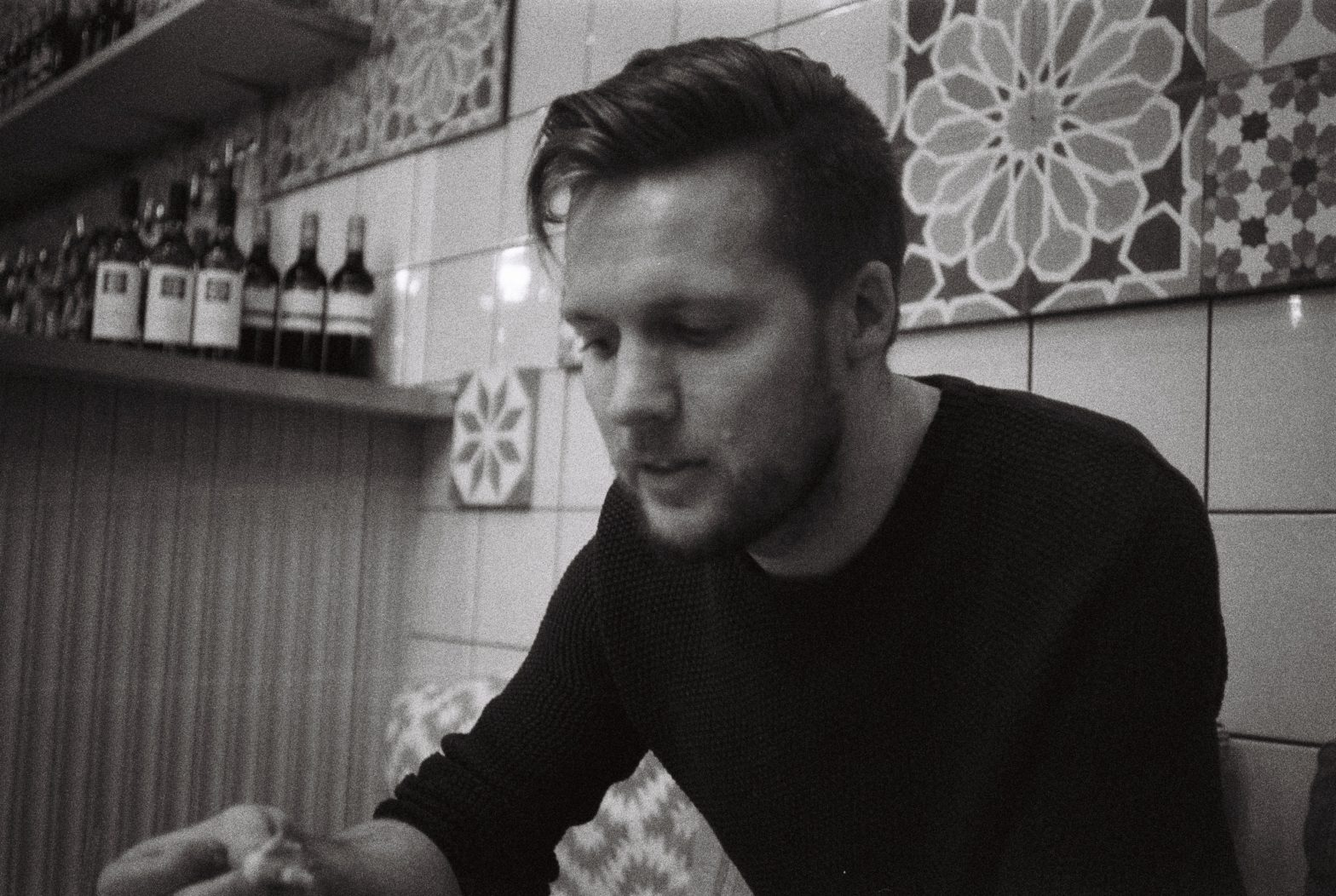 A black and white portrait of coxy (Matt Cox) sitting in front of a tiled wall in a cafe