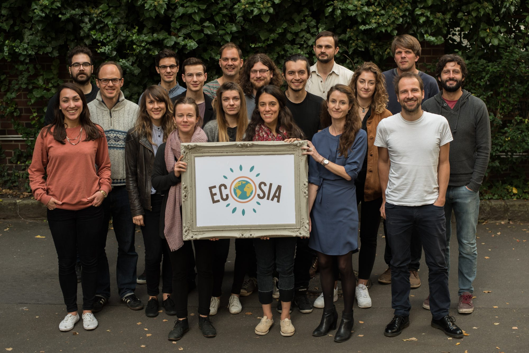 A group photo of 18 smiling and happy people - employees at the company Ecosia - the front three of whom are holding a framed Ecosia company logo.