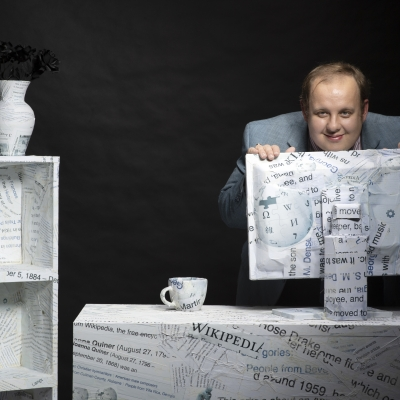 A photo of Steven Pruitt leaning over a computer monitor wrapped in Wikipedia branded paper.