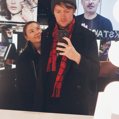 A portrait photo of coxy and Ine Vestengen in a make-up store, surrounded by bright lights and advertising for commercial brand makeups.