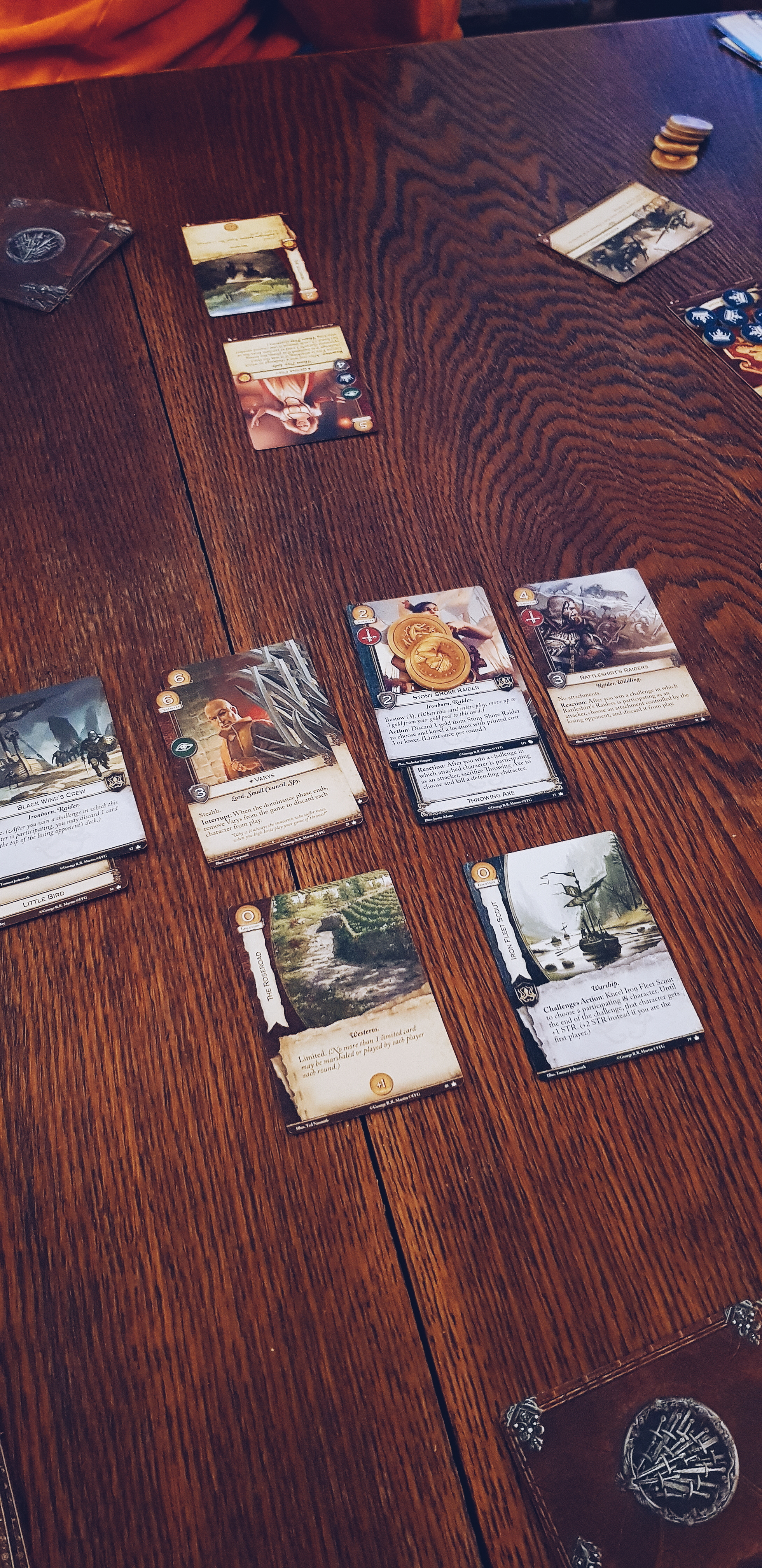 A photo of some playing cards laid out on a wooden table. The game is a Game of Thrones living card game.