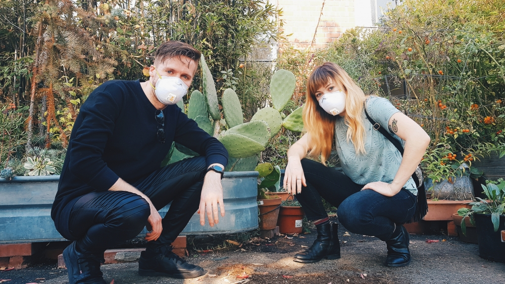 A photo of coxy (left) and Kelly Mason (right) both crouching down infront of some cactus and wearing masks over their mouth
