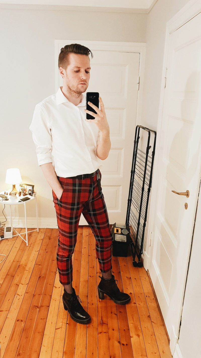 A self-portrait of coxy wearing red check-pattern chino trousers together with a white buttoned shirt and a pair of black Dr Marten Persephone boots