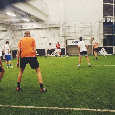A photo of a small indoor football pitch with a group of boys mid-game, kicking a ball around the surface of the artificial grass.