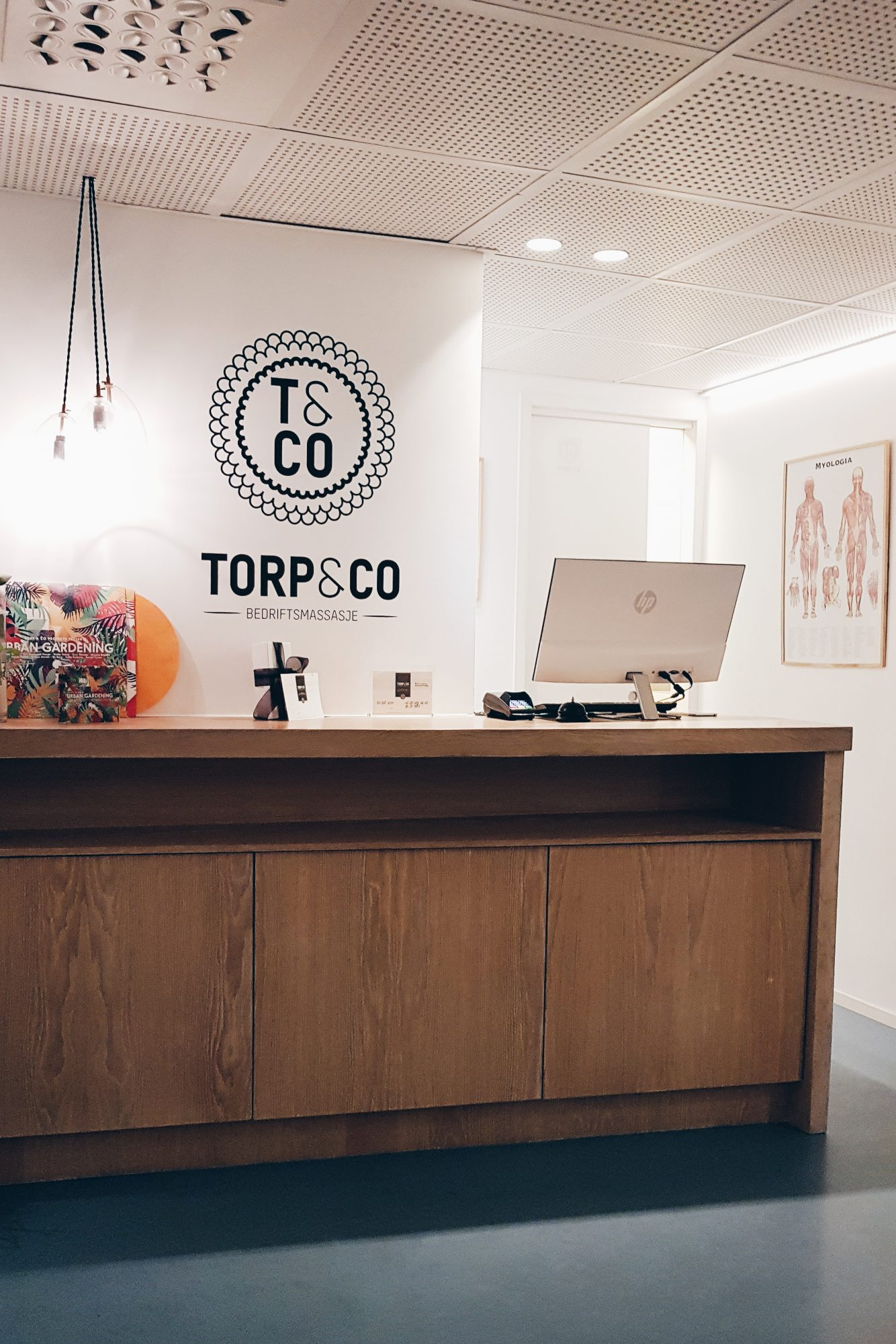 "A photo of a reception area showing a computer perched on the reception desk alongside the company logo which reads ""Torp&Co - bedriftsmassasje"""