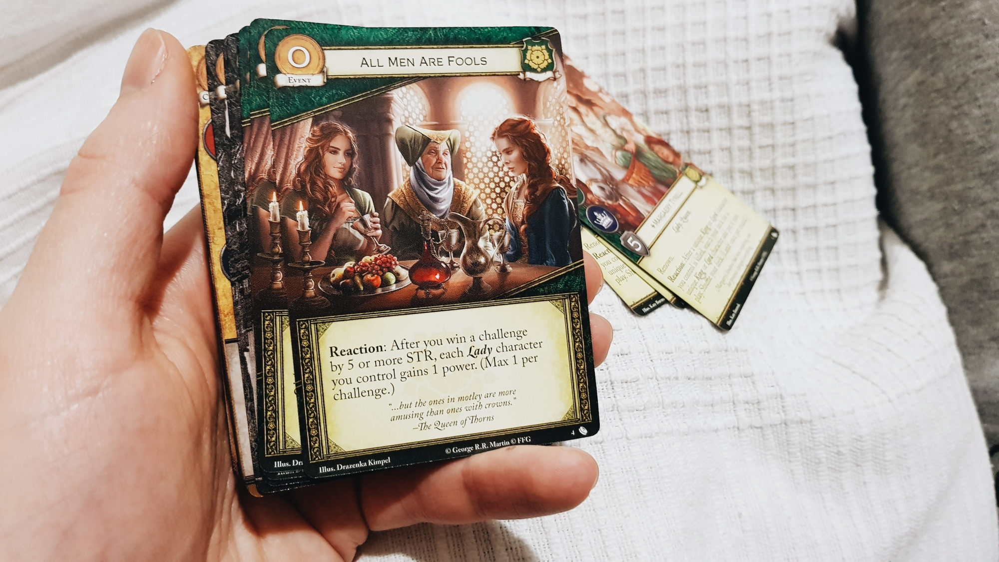 A photo of the card All Men Are Fools from the expansion pack of the same name as part of the Game of Thrones Card Game series. The card shows three ladies sat around a table.