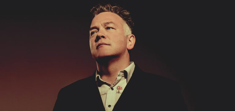A portrait of stand-up comedian Stewart Lee, wearing a black jacket and looking serious against a dark red background.