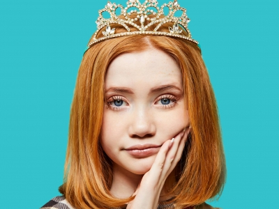 A portrait of a young ginger teenage girl with ginger hear down to her shoulders. She wears a crown on a her head and a non-plussed look on her face as she rests her head in her hand.