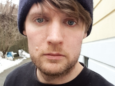 A photo of coxy (Matt Cox) looking sraight into the camera, wearing a navy blue beanie hat with a stiched on Carrahatt logo, covering his hear which peaks through underneath, swept across his forehead and slight whisping over his eyes. He is outsite, stood by a beige apartment block.