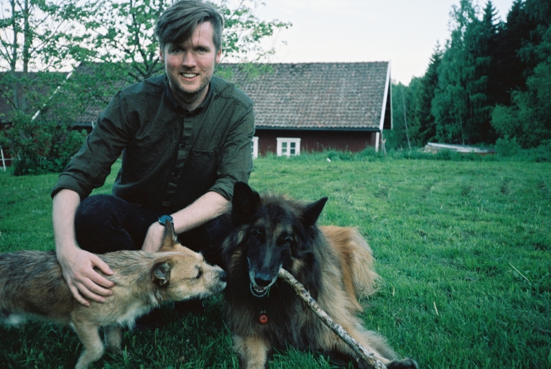 A portrait of coxy (Matt Cox) playing wit two dogs on some grassland in front of a stables.