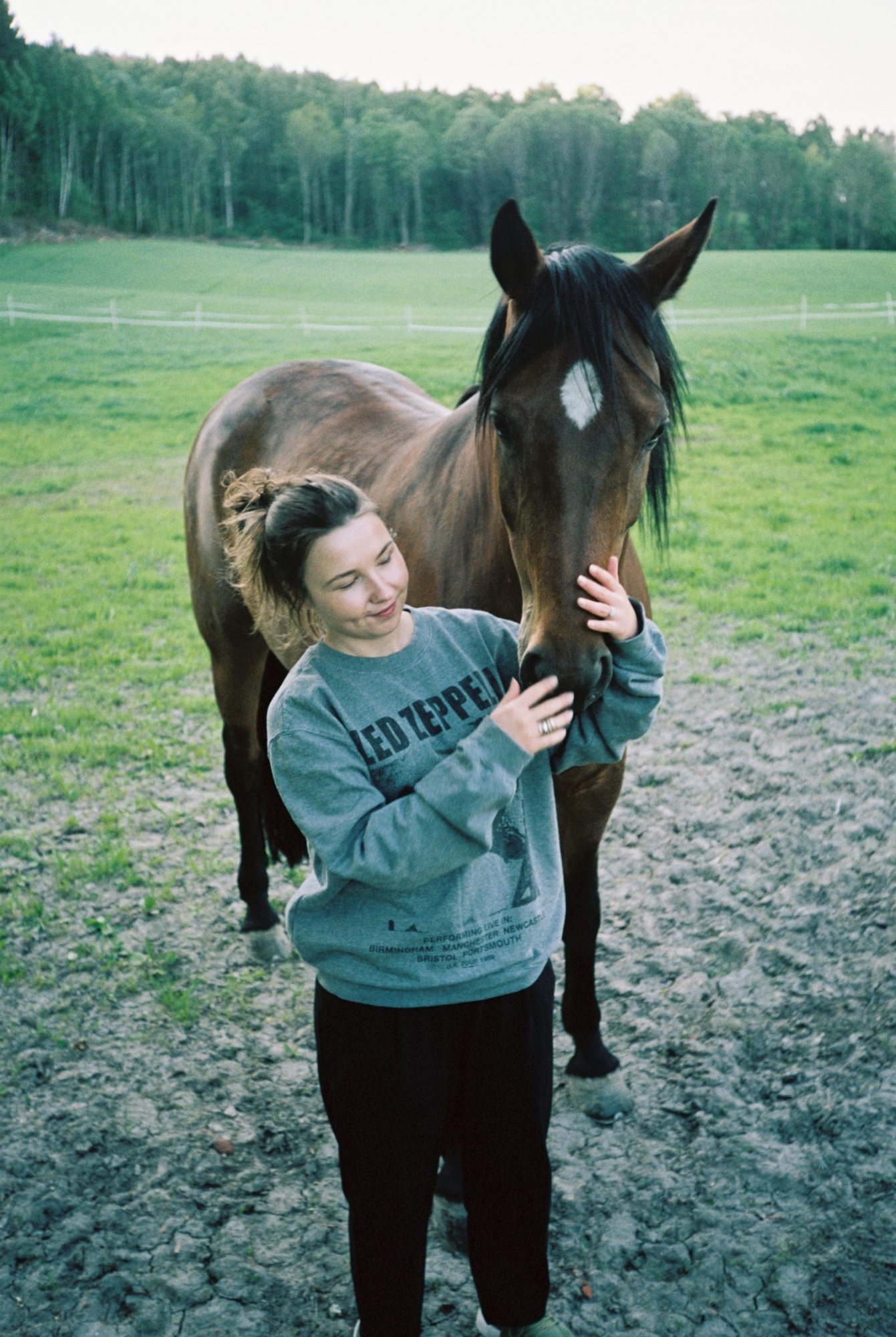 A portrait of Ine, a Norwegian girl, holding the nose of a horse. They are stood in a field together.