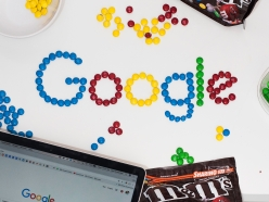 A photo of the Google logo made from coloured candy lay on a desk next to a laptop computer