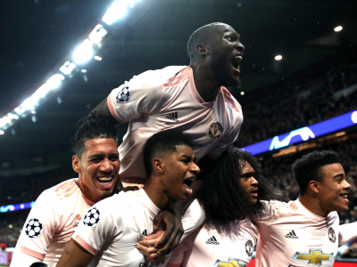 Several Manchester United players celebrate on the pitch after victory over PSG in the Champions League