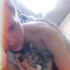 A photo of coxy lay in bed cuddling with a cute kitten, who is sleeping in his arms.
