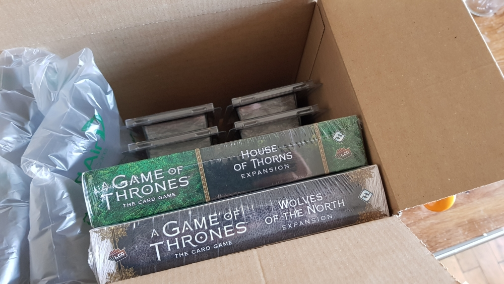 Some card packages from Game of Thrones: The Card Game series packaged in a cardboard box