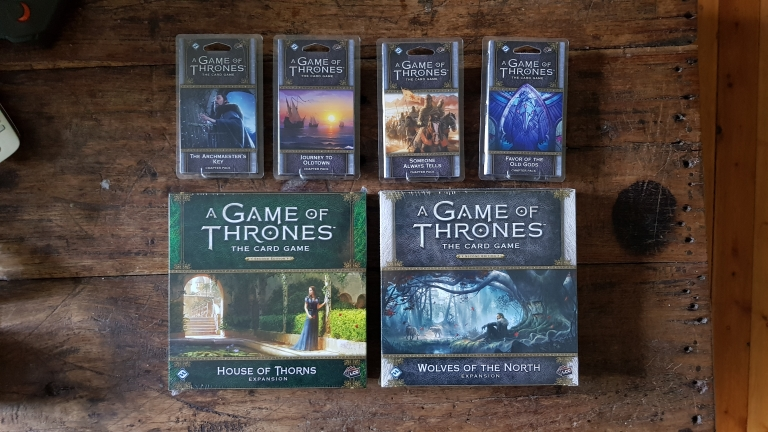 A photo of several boxed card collections, each part of the A Game of Thrones: The Card Game series.