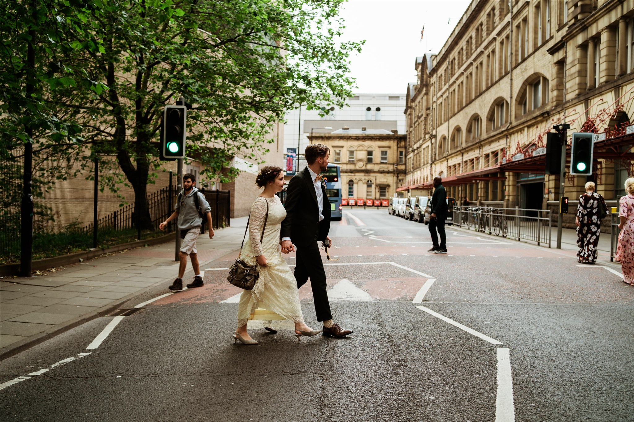 A newly married couple cross the street after leaving their wedding ceremony