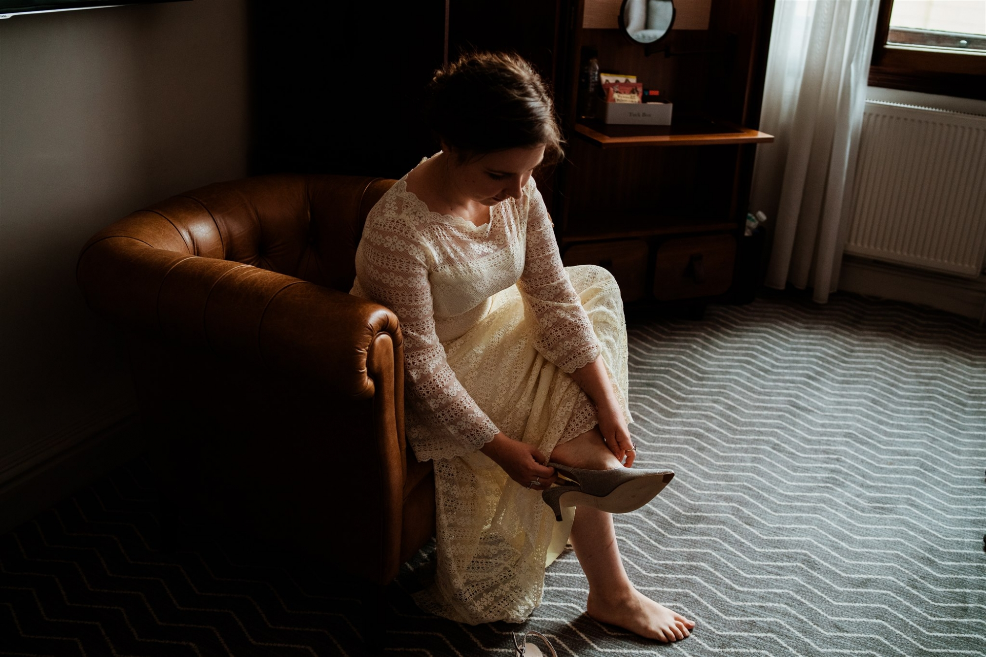 A picture of a bride putting her shoes on before the big day