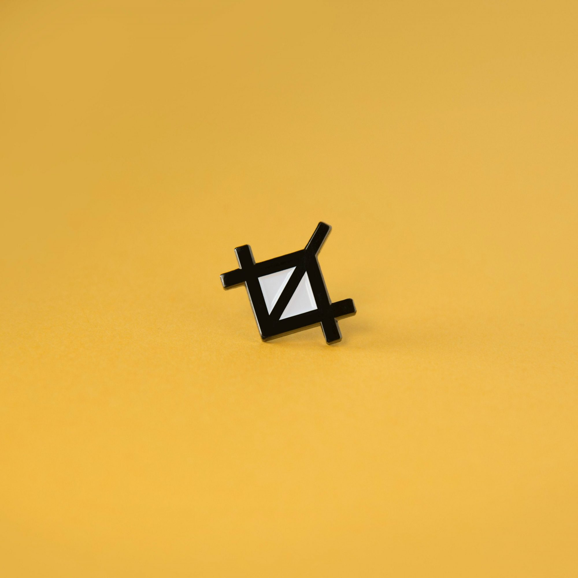 A photo of an enamel pin badge that resembles the crop option in design tools