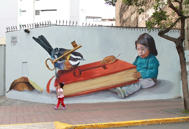 A young girl dressed in pink and red passes a wall featuring a mural of a bird pulling a key out from a book.