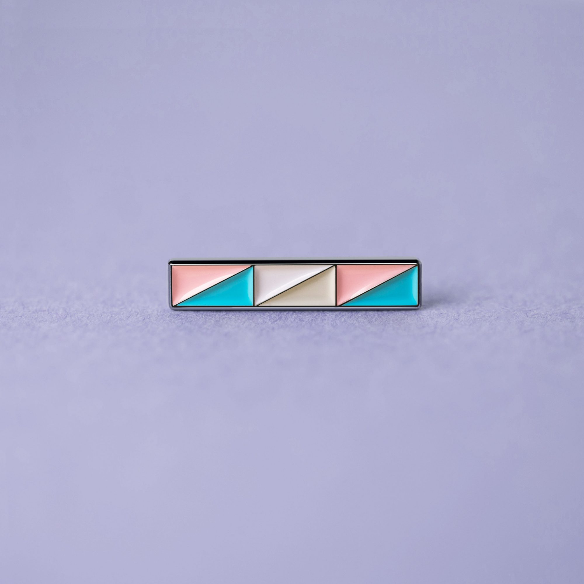A close up photo of a transgender flag pin badge