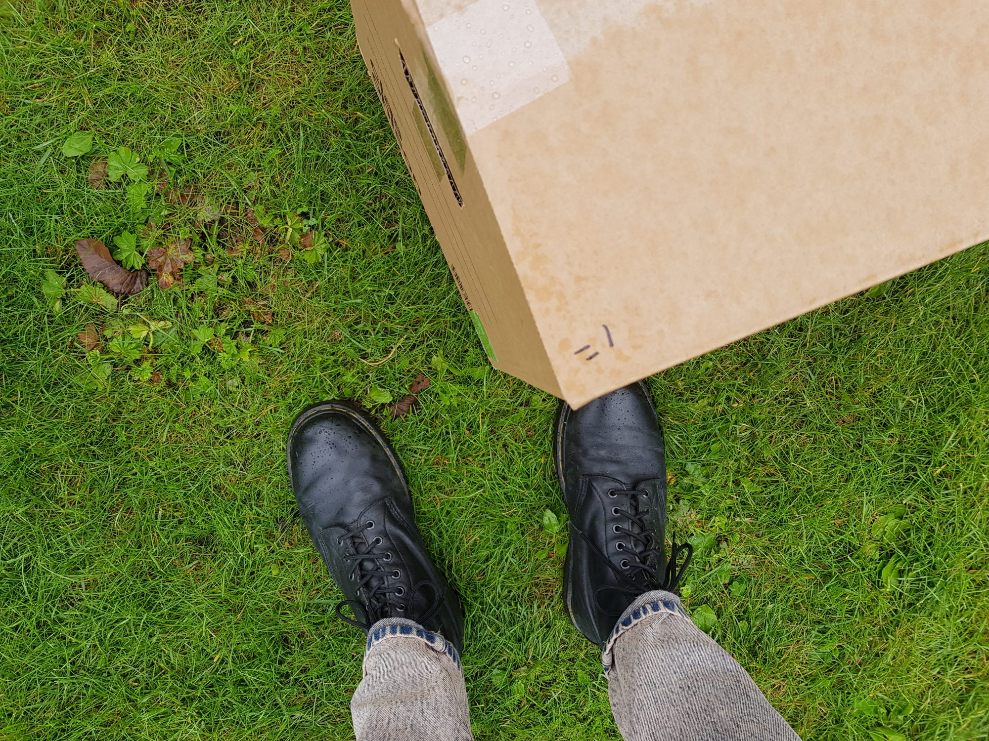 A photo of some legs wearing jeans and Doc Marten boots, stood next to a cardboard box, placed on a grass surface.