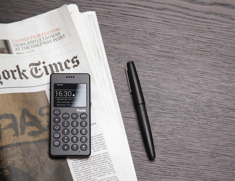 A 3D rendering of the Punkt. MP01 mobile phone on a copy of the New York Times newspaper, sat alongside a pen.