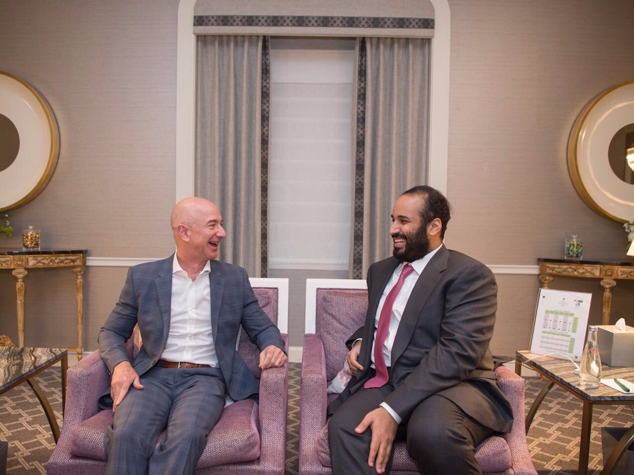 A picture of Saudi Arabia's crown prince meeting Jeff Bezos. They both are sitting in what looks like a hotel room, dressed in suits and laughing together.