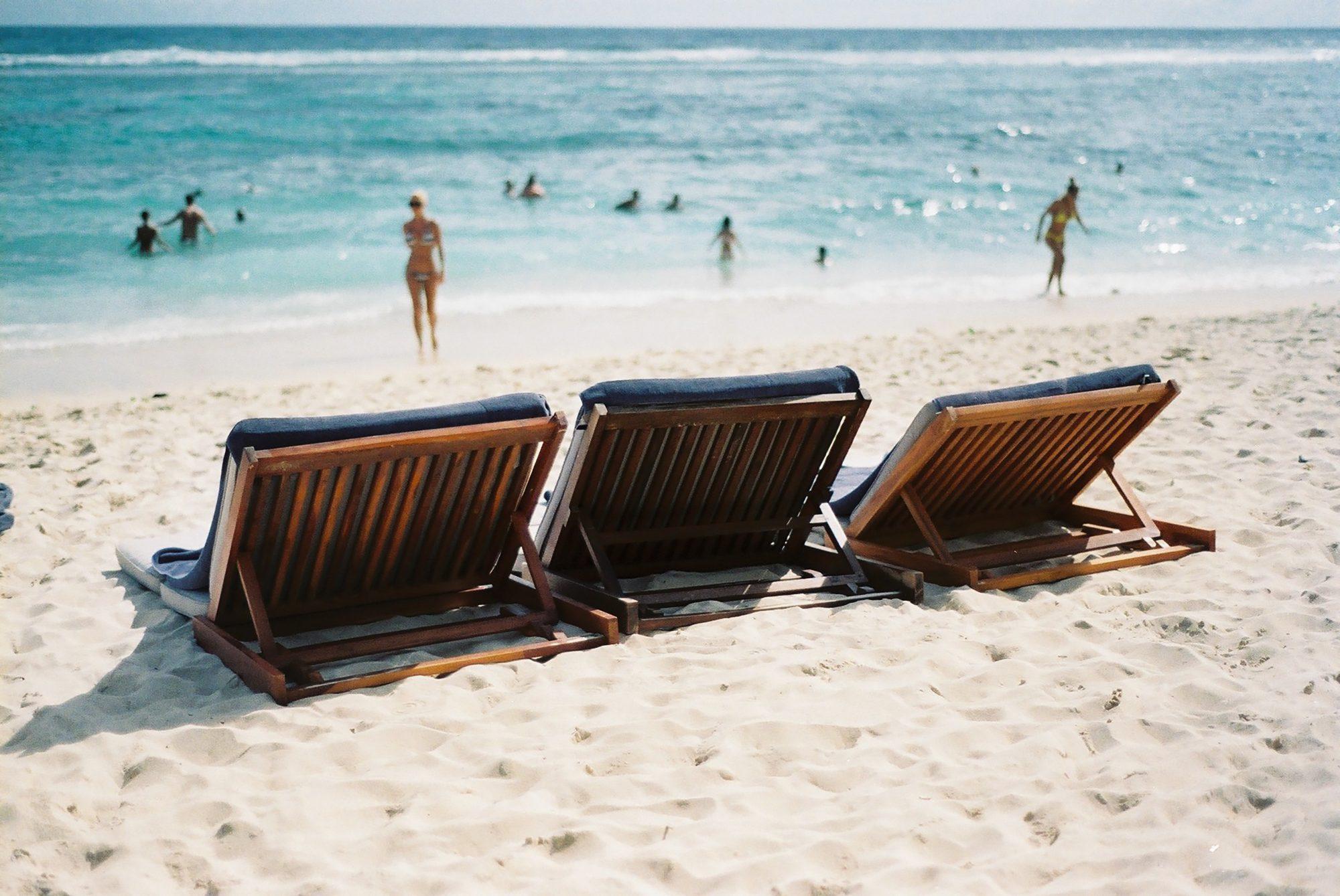 Three deck chairs on a beach