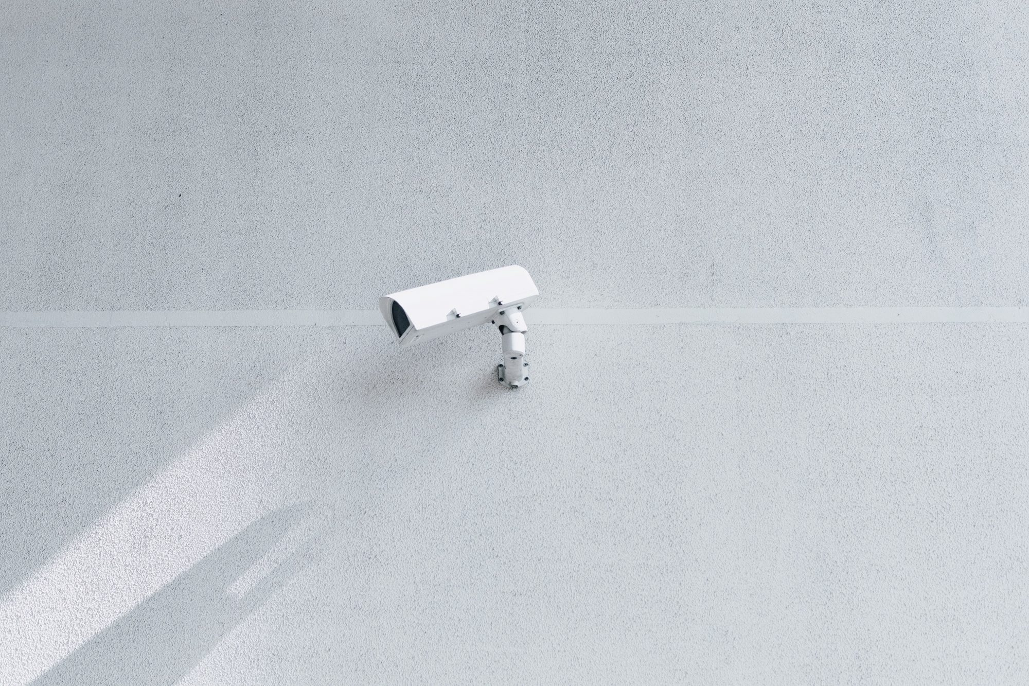 An image of a security camera attached to a blank wall