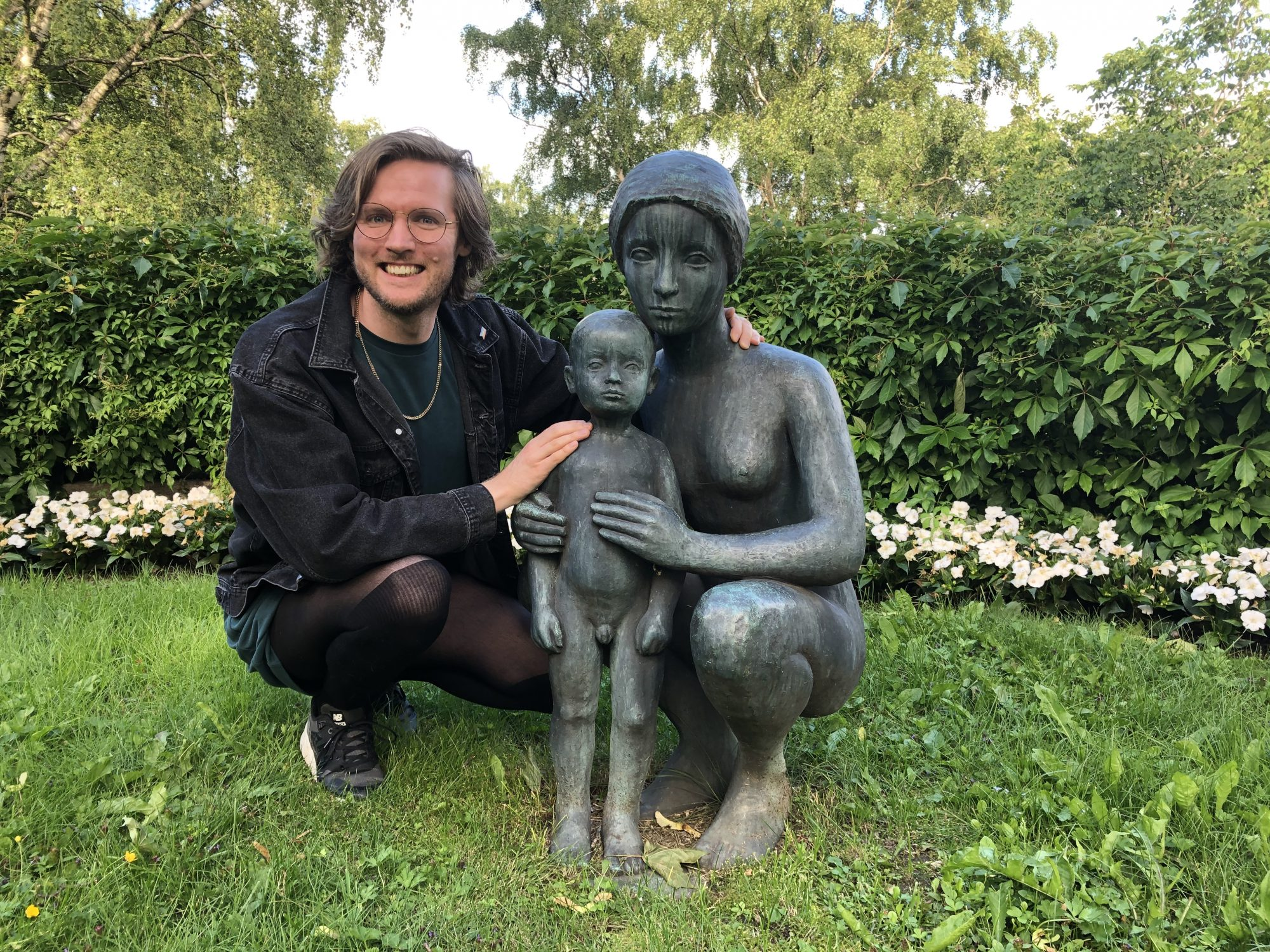 A photo of Matt posing with a statue in a graveyard of a sad lady holding a sad child.