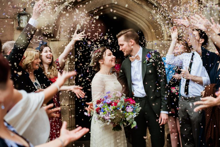 A photo of Matt and Ine leaving Chetham's Library down a tunnel of friends and confetti