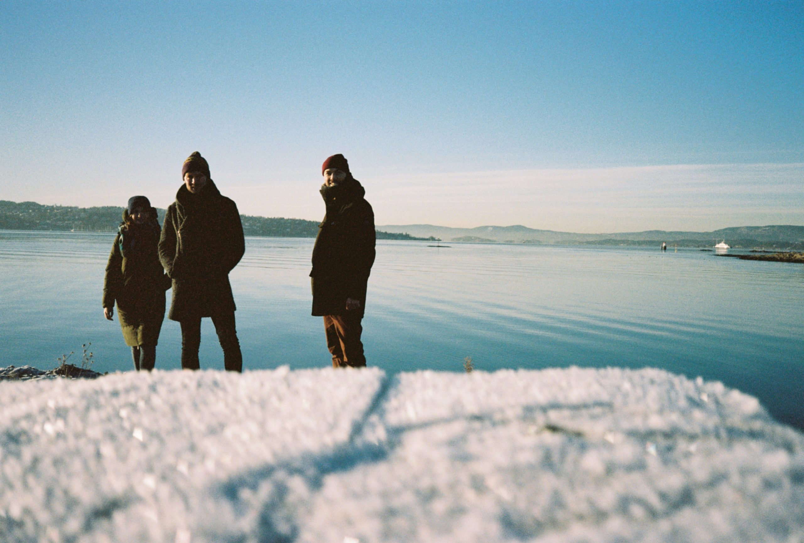 A photo of three people in front of a frozen Oslo fjord. These people are (from left to right) Iga, Matt, and Ben James Wood