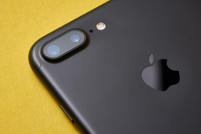 A photo of an iPhone on a yellow background