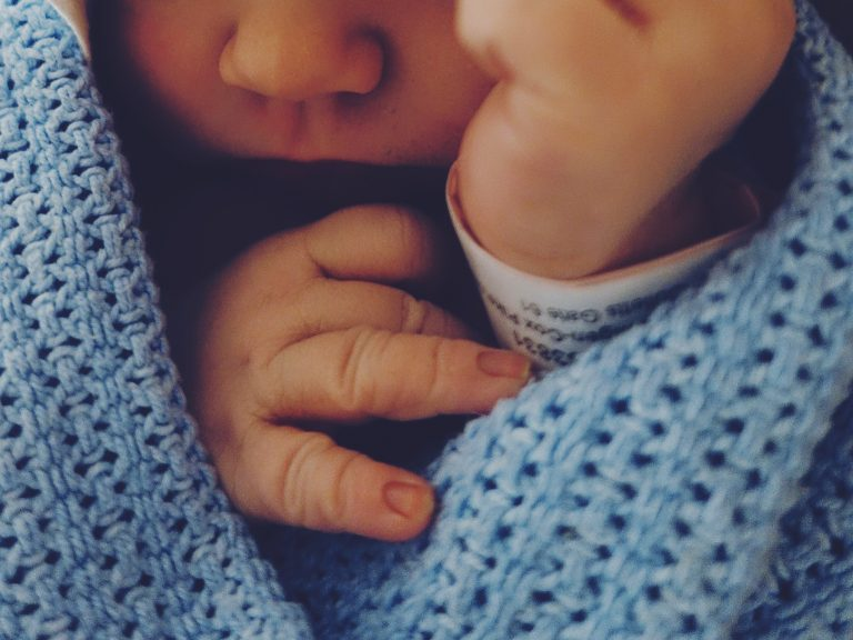 A close up photo of a baby, showing hands and nose and chin. The baby is wrapped in a blue blanket.